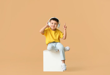 Cute little boy listening to music on color background