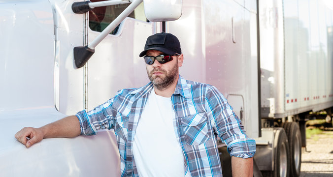 Sharp looking american truck driver wearing blue plaid shirt and black baseball cap with american flag stands next to big rig. Casual dressed trucker on job, blue collar occupations in USA.