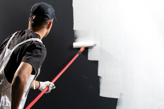 Male decorator painting a wall