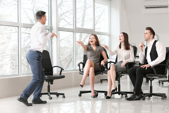 Team of business people playing charades in office