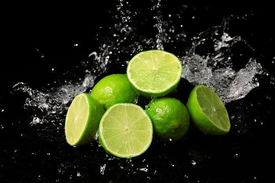 Fresh limes with water splashes on dark background