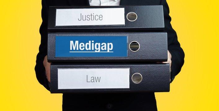 Medigap – Lawyer carries a stack of 3 file folders. One folder has the label Medigap. Symbol for law, justice, judgement