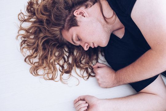 view of young man with blond curly long hair, eyes closed lying down