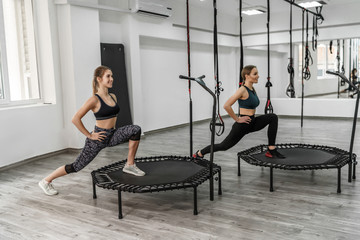 Photo of two active girls and fitness trainer in sport clothes doing exercises for stretching with...