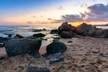 dramatic sunrise on the sea shore. waves crashing rocks on sandy beach. beautiful cloudscape above the horizon