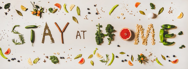Stay at home lettering made from various healthy food ingredients. Flat-lay of stay at home words for quarantine isolation during coronavirus pandemic. Banner for website for food shop