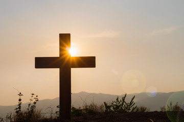 Silhouettes of crucifix symbol with bright sunbeam on the colorful sky background