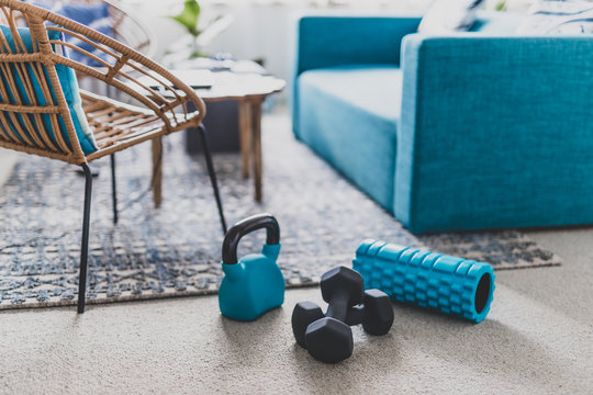 home gym and exercising indoor concept, set of fitness gear on living room carpet next to the couch