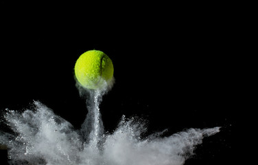Tuinposter Bol tennis ball on black background. concept photo of chalk dust from hitting the line
