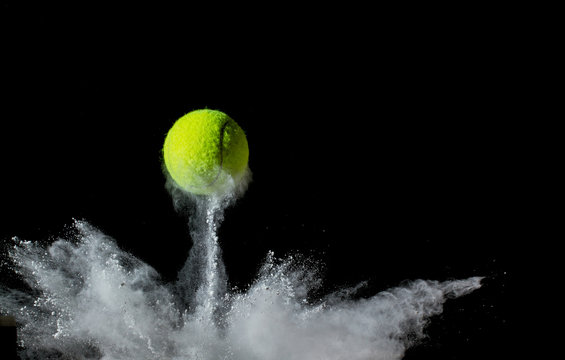 tennis ball on black background. concept photo of chalk dust from hitting the line