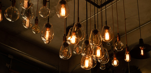 House interior of loft and rustic style. Beautiful vintage luxury light bulb hanging decor glowing in dark. Retro filter effect style. Blend of history and modern. Wall mural