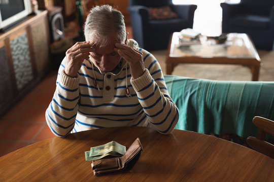 Senior man sitting at table at home and counting his money