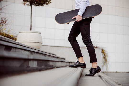 Cropped picture of handsome man in shirt climbing up the stairs outdoors and holding skateboard under armpit.