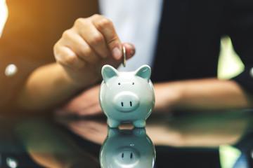 A woman putting coins into piggy bank for saving money concept
