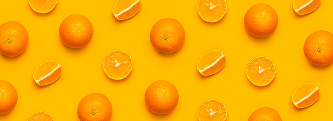 Fresh juicy whole and sliced orange on bright yellow background. Fruit pattern, creative summer concept. Flat lay Top view. Minimalistic background with citrus fruits, vitamin C. Pop art design Banner