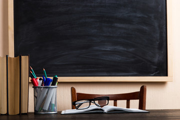 Books, pens, pencils and glasses on a wooden table, against the background of a chalk board....