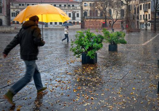 Man With Yellow Umbrella Walking On Street During Rainy Season In City