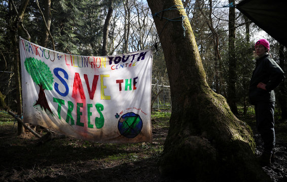 Anti-HS2 campaigner Penny McGregor stands near an Anti-HS2 banner in a protest camp surrounded by trees set to be felled to make way for Britain's HS2 high-speed railway project in ancient woodland in South Cubbington Wood near Leamington Spa