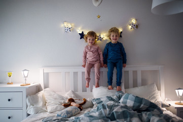 Wall Mural - Two small children playing on bed indoors at home, having fun.