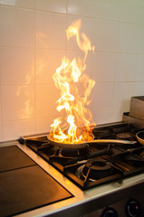 Pan on fire in kitchen presenting fire hazard