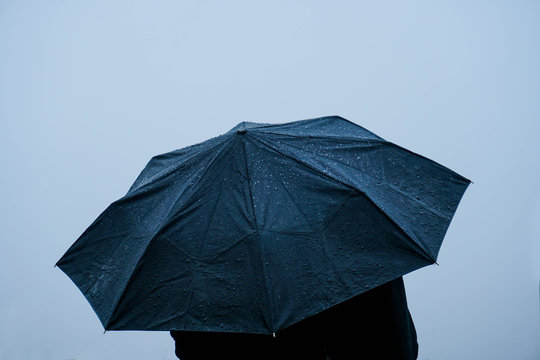 Alone man standing out in rain with an umbrella