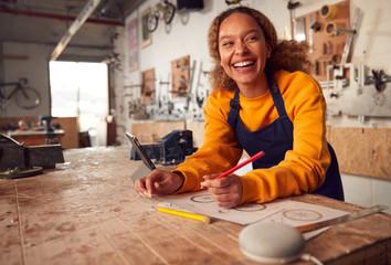 Female Craftsman In Carpentry Workshop For Bamboo Bicycles Using Digital Tablet And Smart Speaker Fotobehang