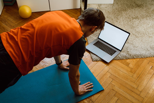 Fitness online exercise. Man training from internet at home. A sporty man in sportswear working out doing arm plank. Mockup blank modern laptop screen. Video live streaming Stay home workout