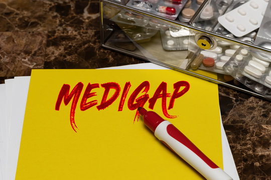 Medigap is written in red letters on a yellow sheet lying on the table next to a box of pills.