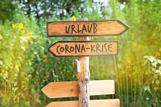 Wooden direction sign with the German words vacation and Corona crisis (Urlaub, Corona-Krise)