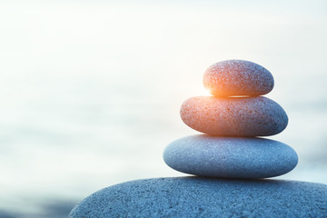 Poster de jardin Zen pierres a sable rock pebble pyramid, zen stones on sea beach at morning sunrise, meditation, spa, harmony, calm and balance concept, copy space