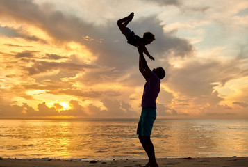 Wall Mural - Father throws up son in the air on beach at sunset
