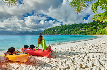 Wall Mural - Woman sitting on kayak at beach, Seychelles, Mahe