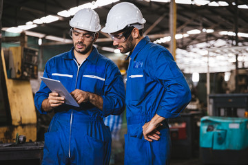 Industry maintenance engineer wearing uniform and safety helmet under inspection and checking production process on factory station by digital tablet. Industry, Engineer, construction concept.