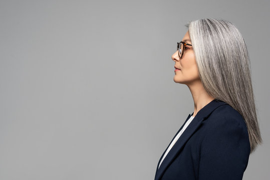 side view of beautiful asian businesswoman with grey hair in eyeglasses isolated on grey