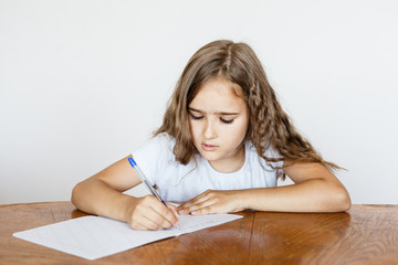 A school girl does homework at home, classes via the Internet, online, learning a foreign language, learning English, notebook, learn letters and words
