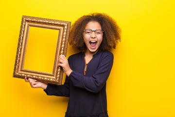 african american little girl  against flat wall holding a baroque frame