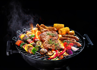 Assorted delicious grilled meat with vegetables on barbecue isolated on black background