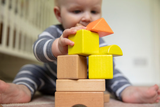 A 7 month old baby pushing over a stack of wooden play blocks