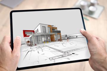 Tablette numérique tenue en main par un architecte qui travaille et réalise l'esquisse d'un projet de construction d'une maison en 3D