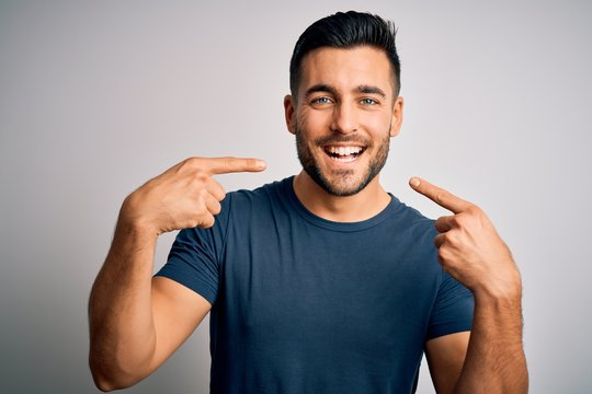 Young handsome man wearing casual t-shirt standing over isolated white background smiling cheerful showing and pointing with fingers teeth and mouth. Dental health concept.