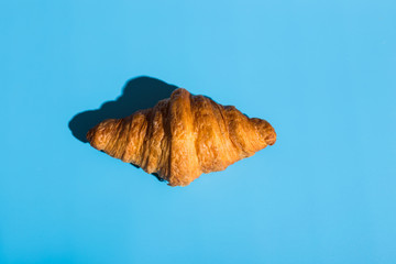 Bakery products baked croissant. Blue background, top view. Pop art style. Delicious and food concept.