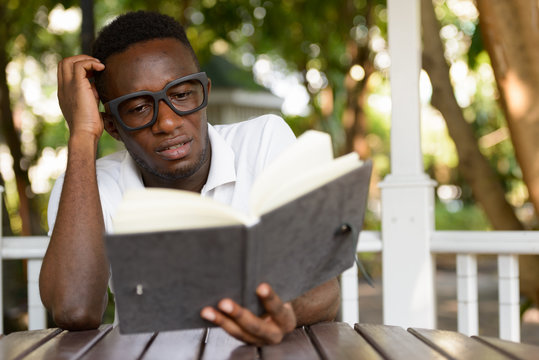 Stressed young African man as student reading book and scratching head at the park