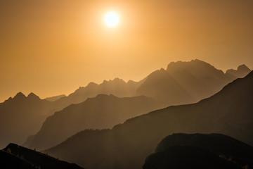 Wall Mural - Sun glow in evening hazy sky and mountain silhouettes view