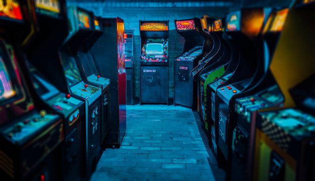 Arcade video games in an empty dark gaming room with purple light with glowing vintage displays and beautiful old retro design