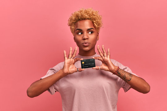 Portrait of a beautiful young African American woman with blond curly hair wearing lilac clothes holding a credit card with clipping path, looks away, thinking about purchases, isolated over pink wall