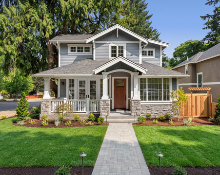 New luxury home exterior with covered porch and green grass on bright sunny day with blue sky