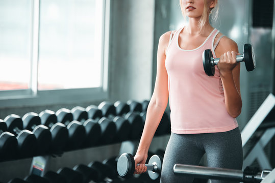 Beautiful Caucasian Sport Woman Lifting Dumbbells and Workout Exercises in Gym - Lifestyle and Healthcare Concept