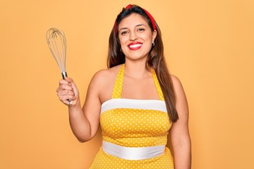 Young hispanic pin up woman wearing fashion sexy 50s style holding cooking whisk blender with a happy face standing and smiling with a confident smile showing teeth