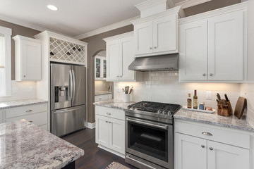 Kitchen Detail in New Luxury Home with Stainless Steel Oven, Gas Range, and Refrigerator