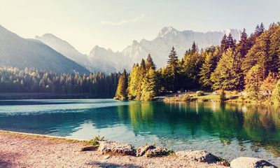 Fotomurales - Picturesque rocky peaks and  turquoise Lake Fusine under sunlight. of the Dolomites lake, Italy. Europe. Instagram filter. Creative image. Amazing nature landscape.